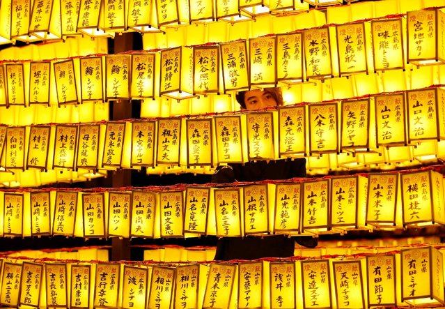 """A man stands between thousands of paper lanterns, which were displayed and lit up the precincts of the shrine, where more than 2.4 million war-dead are enshrined, during the Mitama Festival at Yasukuni Shrine in Tokyo, Japan July 13, 2016. """"Mitama"""" is a respectful word that means """"the soul of a dead person"""" in Japanese, and this """"Soul Festival"""" honors just that. The Yasukuni Shrine is dedicated to the honoring of the souls of those who gave their lives to defend Japan, and this festival is an early step towards the Japanese holiday season of Obon, during which Japanese people honor their deceased ancestors. (Photo by Issei Kato/Reuters)"""