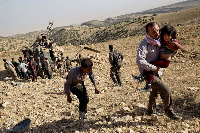 A child is carried away from the crash of an Iraqi military helicopter that was delivering supplies to Yezidis still trapped in Iraq's Sinjar mountains, on August 12, 2014. The Kurdish pesh merga pilot died in the crash, but others aboard were picked up later by other rescue helicopters. (Photo by Adam Ferguson/The New York Times)