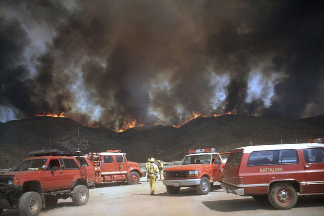 From a turnout on Interstate 5, firefighters approach a ridgeline that had erupted in flame in the Angeles National Forest about 12 miles north of Castaic, Calif., on Wednesday, August 28, 1996. (Photo by Mike Meadows/AP Photo)