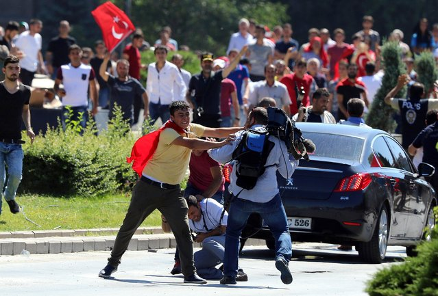 Supporters of Turkey's President Recep Tayyip Erdogan, who were staging a protest against a coup, clash with Turkish journalists near the Turkish military headquarters, in Ankara, Turkey, Saturday, July 16, 2016. (Photo by Ali Unal/AP Photo)