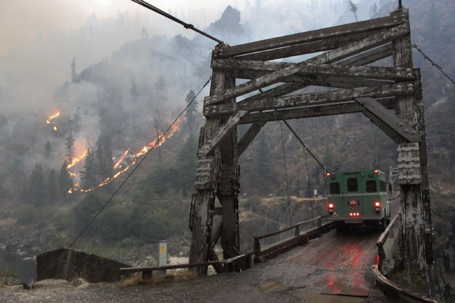 The TePee wildfire is seen burning at the Manning Bridge as it crosses the Salmon River near Riggins, Idaho, in this U.S. Forest Service picture taken August 29, 2015. An 18-mile (29-km) portion of the Salmon River east of the Oregon border was closed to boating and fishing due to the Tepee Springs fire, which has charred more than 78,000 acres (316 square km) of the Payette National Forest and surrounding timber. (Photo by Don Jaques/Reuters/US Forest Service)
