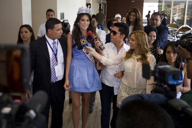 Miss Venezuela 2012 Maria Isler (front 3rd L) talks to the media as she arrives at a news conference in Caracas August 31, 2012. Isler will represent the country in the 2013 Miss Universe pageant. (Photo by Carlos Garcia Rawlins/Reuters)