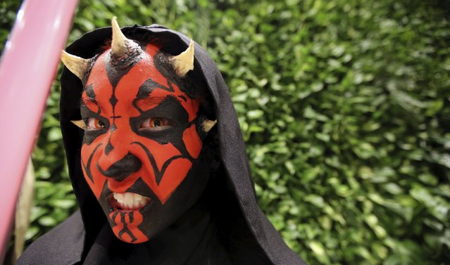 """A woman dressed as the character Darth Maul attends the rollout of products in advancement of the film """"Star Wars: The Force Awakens"""" on """"Force Friday"""" in Sao Paulo, Brazil, September 4, 2015. (Photo by Paulo Whitaker/Reuters)"""