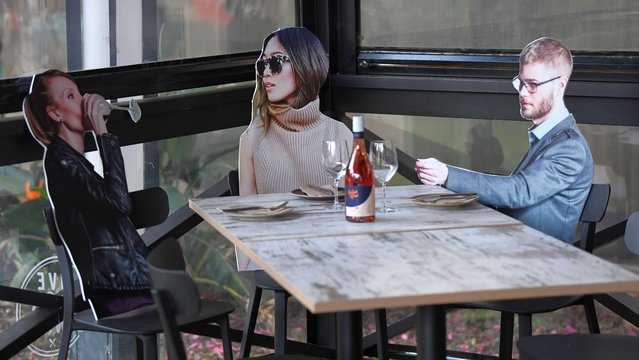 """Cardboard cutouts of human beings sitting at tables inside the Five Dock Dining restaurant on May 14, 2020 in Sydney, Australia. Restaurants and cafes in New South Wales are preparing to reopen with social distancing measures in place as the state government relaxes COVID-19 restrictions. From Friday 15 May cafes, restaurants and hotel dining areas are allowed to reopen but can only seat 10 patrons at a time and for at least four square metres of space per person. To make patrons feel more comfortable and like they are having a regular dining experience, Five Dock Dining owner Frank Angeletta will use cardboard customers to fill the empty space in his restaurant along with having taped background noise simulating guest """"chatter"""" playing for ambience. (Photo by James D. Morgan/Getty Images)"""