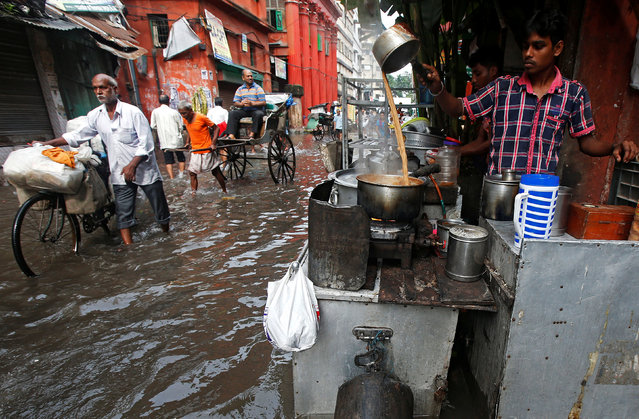 A man prepares tea at a roadside shop on a flooded street in Kolkata, India, August 11, 2016. (Photo by Rupak De Chowdhuri/Reuters)