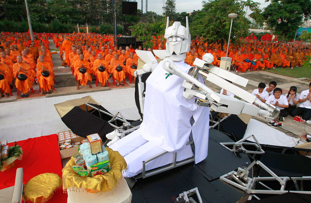 A robot sits before Buddhist monks, as they pray during a mass alms-offering ceremony at King Mongkut's Institute of Technology Ladkrabang in Bangkok, on June 19, 2012. The ceremony was held to mark the 2,600th anniversary of the enlightenment of Lord Buddha. (Photo by Sukree Sukplang/Reuters)