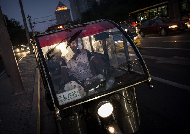 A Chinese auto-rickshaw driver drops off a female passenger in the trendy Sanlitun neighborhood on September 5, 2014 in Beijing, China. (Photo by Kevin Frayer/Getty Images)