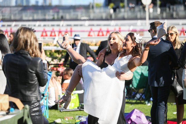 A woman lifts up her pal as the pair pose for a photo on 2017 Derby Day at Flemington Racecourse on November 4, 2017 in Melbourne, Australia. (Photo by Splash News and Pictures)