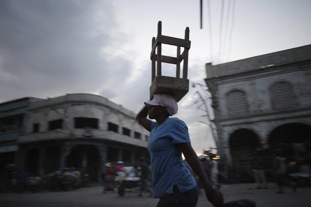 A saleswoman walks carrying a stool at dusk in a street in Port-au-Prince, Haiti, March 7, 2016. (Photo by Andres Martinez Casares/Reuters)
