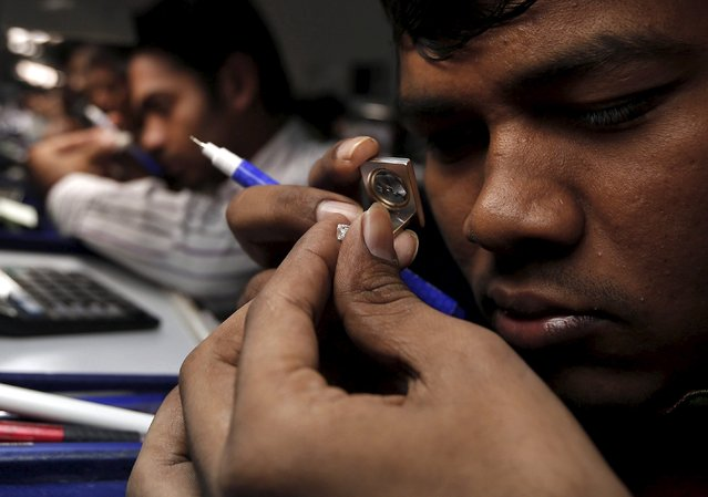A craftsman checks the colour of a diamond at the polishing department of a diamond processing unit at Surat in Gujarat, India, August 31, 2015. (Photo by Amit Dave/Reuters)