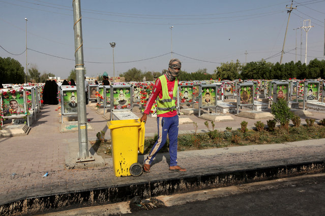 """A municipality worker pulls a trash container at the Wadi al-Salam cemetery, Arabic for """"Peace Valley"""", in Najaf, south of Baghdad, Iraq, August 5, 2016. (Photo by Alaa Al-Marjani/Reuters)"""