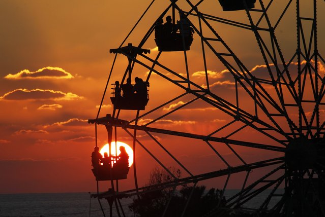 People ride a Ferris wheel in an amusement park as they celebrate the first day of Eid al-Adha, at the port-city of Sidon, southern Lebanon October 4, 2014. (Photo by Ali Hashisho/Reuters)