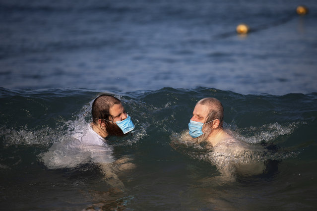 Ultra-orthodox Jewish men wearing protective face masks swim in the Mediterranean Sea, on a beach segregated for males three days a week, in Tel Aviv, Israel, Wednesday, July 8, 2020. In an effort to quell the rapid spread of the coronavirus, Israel has re-imposed a series of restrictions on the public. This week, the Israeli government limited gatherings and ordered reception halls, restaurants, bars, theaters, fitness centers and pools be shut down again. (Photo by Oded Balilty/AP Photo)