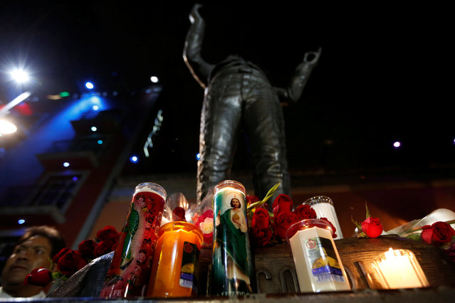 Candles are seen next to a statue of iconic Mexican singer and song writer Juan Gabriel after his death, in Plaza Garibaldi in Mexico City, Mexico August 28, 2016. (Photo by Carlos Jasso/Reuters)