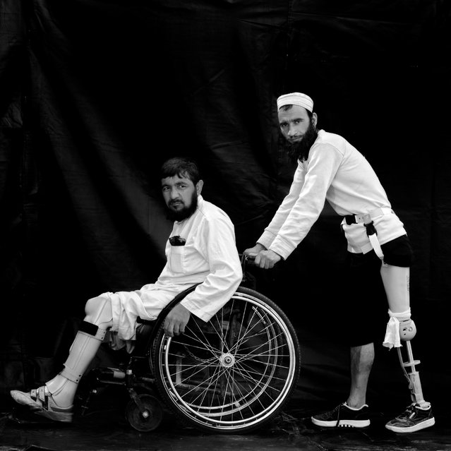(L-R) 30-year-old Gholam Rasool, from Herat who lost his feet 3 years ago after stepping on a land mine, with 35-year-old Mohammad Aref, also from Herat who lost a leg 9 years ago, photographed in December 2010, in Herat, Afghanistan. The UN Mine Information Network (E-MINE), estimates after 30 years of conflict in Afghanistan, approximately 62 people are killed or injured by mines each month in the country. (Photo by Majid Saeedi/Getty Images)