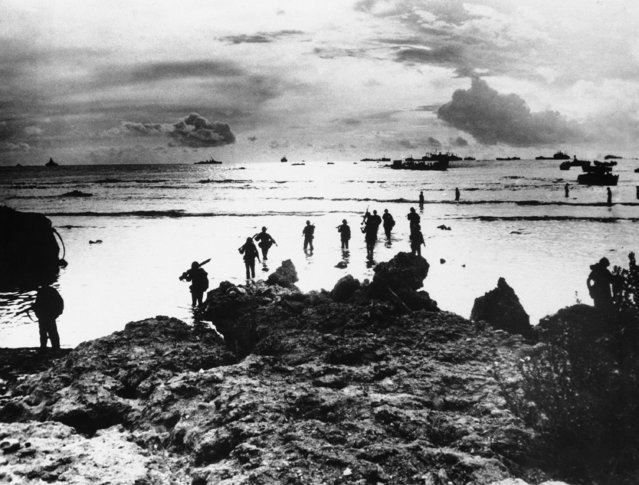 A column of U.S. Marines wade ashore at a Tinian Island beach point, on September 28, 1944, after disembarking from Coast Guard landing craft to reinforce American assault troops fighting inland. In background are vessels of the supporting force and various landing craft. (Photo by AP Photo)