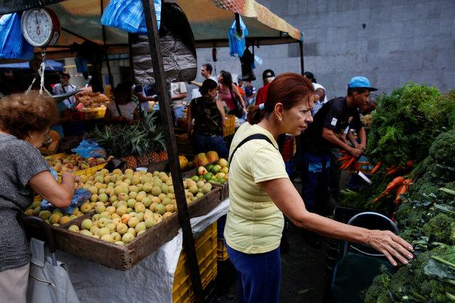 People shop at a vegetable street market in Caracas, Venezuela August 13, 2016. (Photo by Carlos Garcia Rawlins/Reuters)