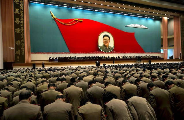 North Korean military officers bow at an image of the late North Korean leader Kim Jong Il during a national meeting of top party and military officials, on the eve of the first anniversary of Kim's death, in Pyongyang, December 16, 2012. (Photo by Ng Han Guan/Associated Press)