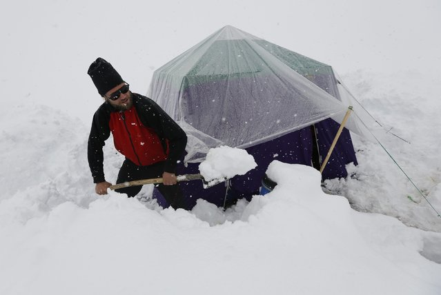 A German trekker removes snow from a kitchen tent at Concordia, the confluence of the Baltoro and Godwin-Austen glaciers, near the world's second highest mountain K2  in the Karakoram mountain range in Pakistan September 5, 2014. (Photo by Wolfgang Rattay/Reuters)
