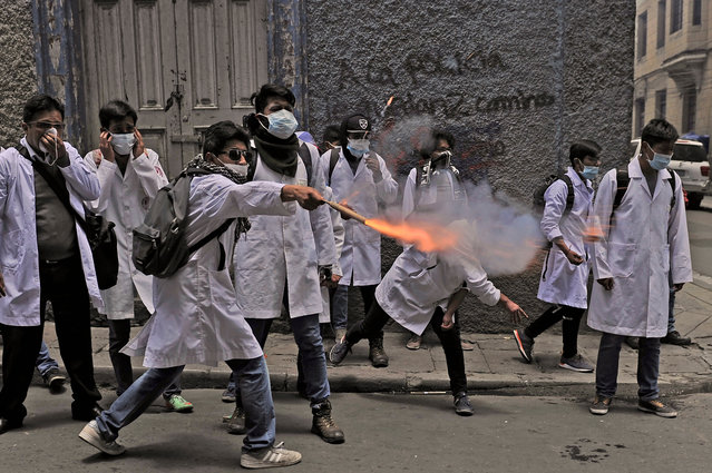 Medicine students clash with riot police officers, during a protest against President Morales new law, that proposes penal sanctions to medical malpractice, near Murilo square in La Paz, on December 19, 2017. Doctors in Bolivia went on hunger strike on Monday, in addition to renouncing to hierarchical positions in public hospitals to protest against President Evo Morales new law which penalizes medical malpractice. (Photo by Jorge Bernal/AFP Photo)