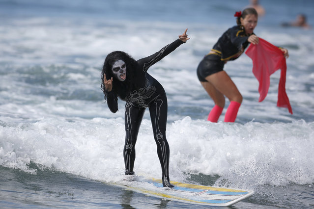 A competitor rides a wave during the 7th annual ZJ Boarding House Haunted Heats Halloween surf contest. (Photo by Lucy Nicholson/Reuters)