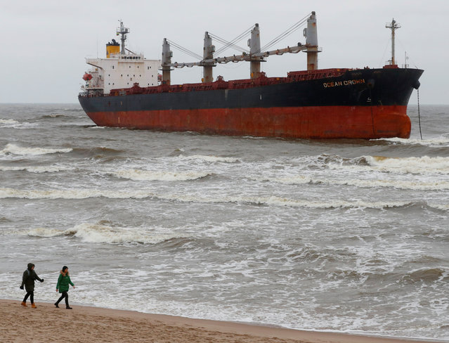 "People walk past stranded cargo ship ""Ocean Crown"" during a windy weather in Klaipeda, Lithuania on December 26, 2017. (Photo by Ints Kalnins/Reuters)"