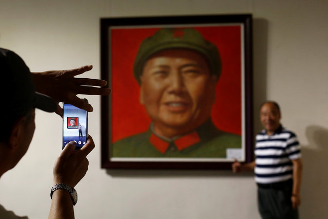 A man poses in front of a portrait of late Chinese Chairman Mao Zedong during the opening of an exhibition of Mao related art in Beijing, China, September 8, 2016. (Photo by Thomas Peter/Reuters)