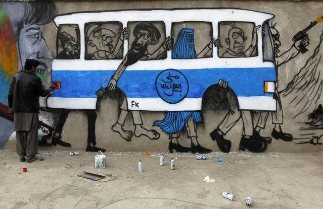 An artist paints graffiti on the wall of an industrial park in Kabul, Afghanistan December 19, 2010. The bus with no wheels and crammed with passengers is a stark comment on war-torn Kabul's appalling public transport. (Photo by Omar Sobhani/Reuters)