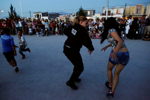 """A police officer dances with a resident, an unconventional approach to connect the police with the community in rough neighbourhoods, as part of the """"Tirando Barrio"""" (Marking territory) programme in Saltillo, Northern Mexico September 9, 2016. (Photo by Daniel Becerril/Reuters)"""