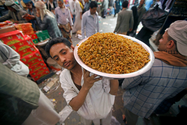 A man carries raisins outside his shop in the old market, ahead of the Eid Al-Adha festival, in the historic city of Sanaa, Yemen September 11, 2016. (Photo by Mohamed al-Sayaghi/Reuters)
