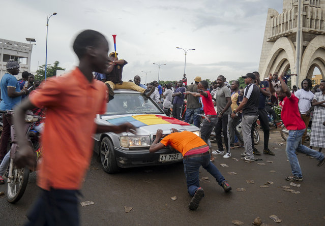 People celebrate in the streets in the capital Bamako, Mali Tuesday, August 18, 2020. Mutinous soldiers detained Mali's president and prime minister Tuesday after surrounding a residence and firing into the air in an apparent coup attempt after several months of demonstrations calling for President Ibrahim Boubacar Keita's ouster. (Photo by AP Photo/Stringer)