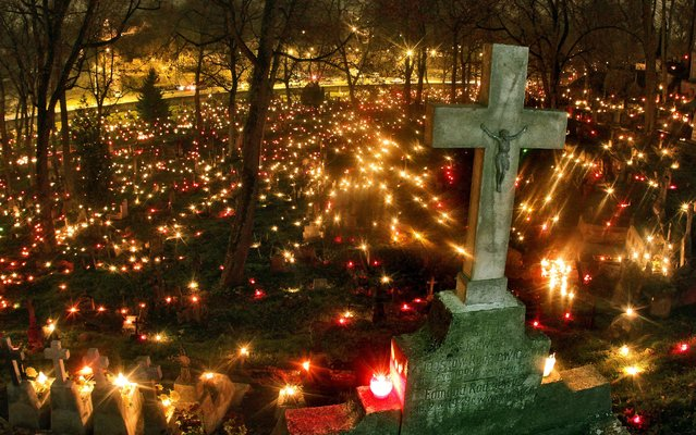 Candles are left on tombs to mark the occasion of All Saints' Day on the Rasos cemetery in Vilnius, Lithuania on November 1, 2014. In Lithuania, people visit cemeteries at this time across the country in memory of the deceased. (Photo by Petras Malukas/AFP Photo)