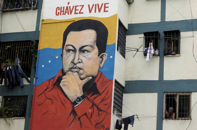 A man looks out a window of a building, next to a mural of Venezuela's late president Hugo Chavez, in Caracas, Venezuela September 8, 2016. (Photo by Henry Romero/Reuters)