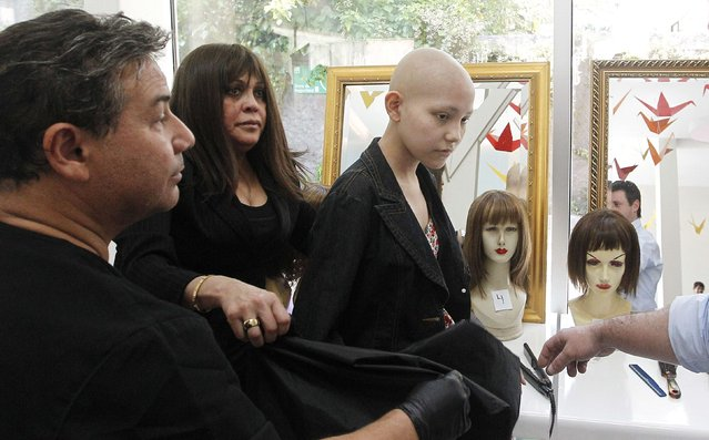 Hair stylist Marcelo Avatte (L) prepares to fit a natural hair wig on Isidora Serrano (R), 14, who lost her hair due to chemotherapy to treat her bone cancer, in the cancer ward of the Luis Calvo Mackenna Hospital in Santiago, October 23, 2014. (Photo by Rodrigo Garrido/Reuters)