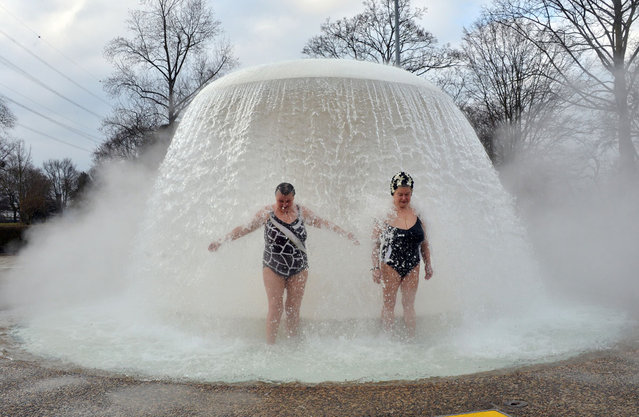 "Two women stand under a fountain in the so-called ""Sonnenbad"" (Sun bath) swimming pool at temperatures just below 0 degrees Celsius during the opening of the pool for the new season Karlsruhe, southern Germany on February 22, 2013. The pool is the first to re-open after being closed for winter. (Photo by Uli Deck/AFP Photo)"