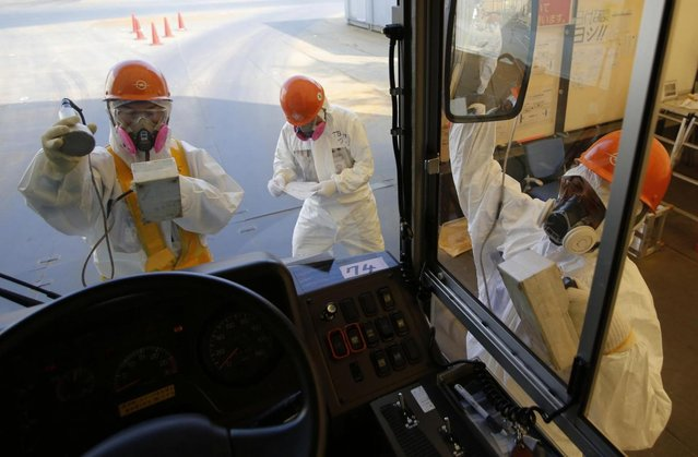 Workers carry out radiation screening on a bus for a media tour at Tokyo Electric Power Co. (TEPCO)'s tsunami-crippled Fukushima Dai-ichi nuclear power plant in Okuma, Fukushima prefecture Wednesday, March 6, 2013, ahead of the second anniversary of the March 11, 2011 tsunami and earthquake. Some 110,000 people living around the nuclear plant were evacuated after the massive March 11, 2011, earthquake and tsunami knocked out the plant's power and cooling systems, causing meltdowns in three reactors and spewing radiation into the surrounding air, soil and water. (Photo by Issei Kato/AP Photo/Pool)