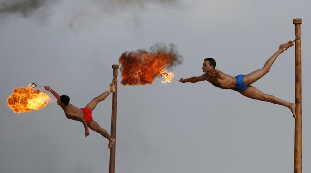Indian army soldiers spit fire as they perform the mallakhamb, a traditional Indian gymnastic sport, during a display of skills at Officers Training Academy in Chennai, India, Friday, March 15, 2013. (Photo by Arun Sankar K./AP Photo