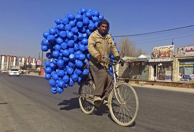 An Afghan man carries plastic cans for sale in Kabul, Afghanistan, Friday, January 5, 2018. (Photo by Rahmat Gul/AP Photo)