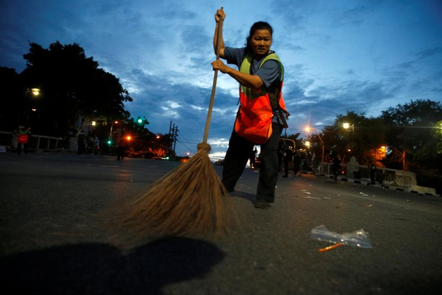 A cleaner sweeps up trash on a street after an anti-government protest on the 47th anniversary of the 1973 student uprising, in Bangkok, Thailand on October 15, 2020. (Photo by Soe Zeya Tun/Reuters)