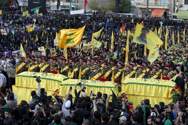 Lebanon's Hezbollah members, supporters and relatives surround the coffins as they attend the funeral of three Hezbollah fighters who were killed while fighting alongside Syrian army forces in Syria in Nabatieh town, southern Lebanon, October 27, 2015. The fighters names are Hussein Hassan Shreifie, Ali al-Akbar Mohamad Khashfeh and Mohamad Saeed Fawaz. (Photo by Ali Hashisho/Reuters)
