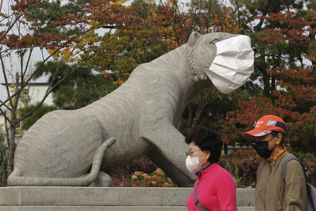 People wearing face masks to help protect against the spread of the coronavirus pass by a statue with a face mask at a park in Seoul, South Korea, Friday, October 16, 2020. South Korea's daily coronavirus tally has dropped below 50 for the first time in more than two weeks despite reports of small-scale local infections. (Photo by Ahn Young-joon/AP Photo)
