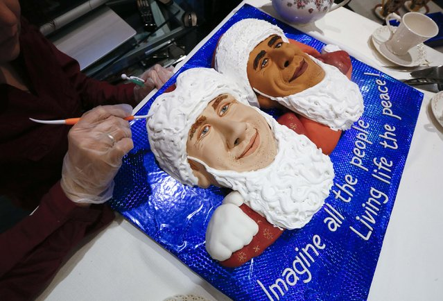 """Russian artist Yelena Zelenskaya puts the finishing touches on a pie she baked to look like U.S. President Barack Obama and Russia's President Vladimir Putin dressed as Santa Claus and Father Frost, before the art performance named """"Sweet Sanctions 2. Five O'Clock Tea With Presidents"""",  during a TV broadcasting of Putin's address to members of parliament and other top officials in the Kremlin, at the Romanov's art gallery in Krasnoyarsk, Siberia, December 4, 2014. (Photo by Ilya Naymushin/Reuters)"""