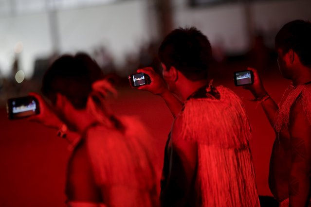 Indigenous men use mobile devices during the closing ceremony of the first World Games for Indigenous Peoples in Palmas, Brazil, October 31, 2015. (Photo by Ueslei Marcelino/Reuters)