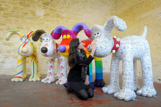 Lauren Vincent, fundraising manager for Gromit Unleashed, poses on April 19, 2013 with four, of around 70, Gromit sculptures painted by (left to right) Sir Paul Smith, Cath Kidston, Richard Williams and Simon Tofield, at a secret location in Bristol before they are placed for public view on an arts trail around the city from July 1st. After the public arts trail the sculptures will be auctioned to raise funds for Wallace and Gromit's Grand Appeal's campaign to raise funds for the expansion of Bristol Children's Hospital. (Photo by Tim Ireland/PA Wire)