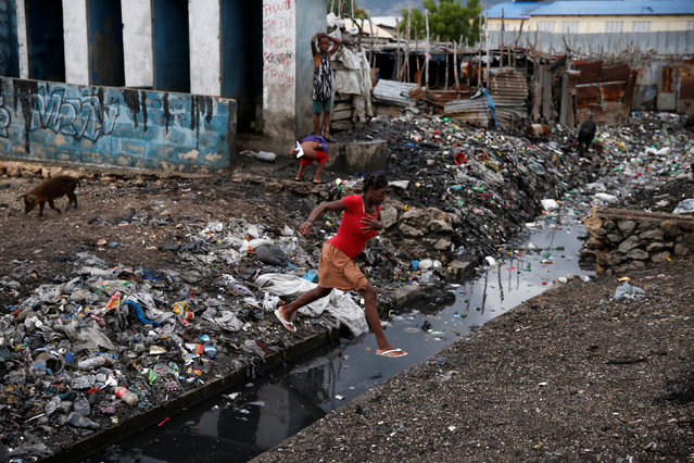 A woman crosses over a water canal after Hurricane Matthew passes Cite-Soleil in Port-au-Prince, Haiti, October 5, 2016. (Photo by Carlos Garcia Rawlins/Reuters)