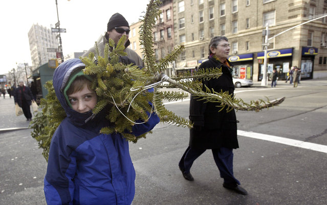 Duncan Herb, left, helps his father Peter Herb, behind at center, carry their Christmas tree home down Sixth Avenue in New York Saturday, December 18, 2004. (Photo by Gregory Bull/AP Photo)