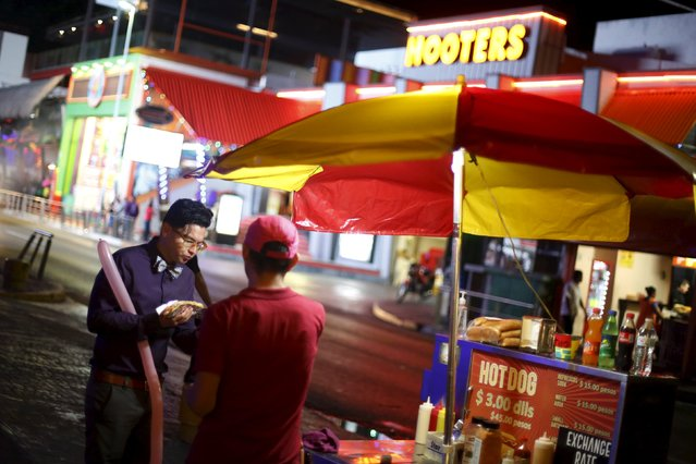 A tourist buys a hot dog on a street in Cancun, October 12, 2015. (Photo by Edgard Garrido/Reuters)