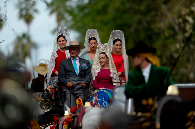 """Participants sporting traditional """"mantillas"""" (shawls) wait for parading in the XXXIII """"Enganches"""" (Horse- drawn carriages) exhibition at the Real Maestranza bullring in Sevilla on April 15, 2018. (Photo by Cristina Quicler/AFP Photo)"""
