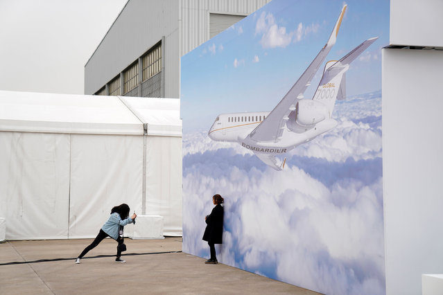 Women take picture in front of a billboard poster of the Bombardier Global 7000 aircraft at the Asian Business Aviation Conference and Exhibition (ABACE) at Hongqiao International Airport in Shanghai, China on April 16, 2018. (Photo by Aly Song/Reuters)