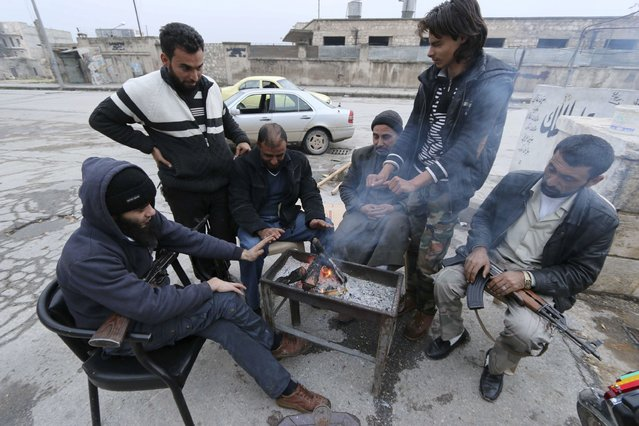 Rebel fighters and civilians warm themselves around a fire in Tariq al-Bab neighbourhood of Aleppo December 28, 2014. (Photo by Abdalrhman Ismail/Reuters)